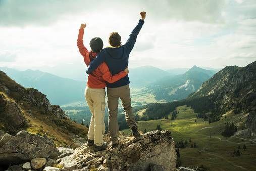Mann und Frau Siegerpose auf dem Berggipfel.jpg